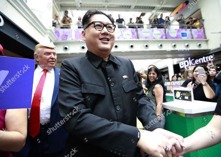 Kim Jong-un impersonator Howard X (R) shakes hands of shoppers as he walks with Donald Trump impersonator Dennis Alan (back,L) as they make an appearance at the Bugis Junction shopping mall in Singapore, 09 June 2018. US President Donald J. Trump and North Korean leader Kim Jong-un are scheduled to meet at the Capella Hotel on Singapore's Sentosa Island for an historic summit on 12 June 2018.