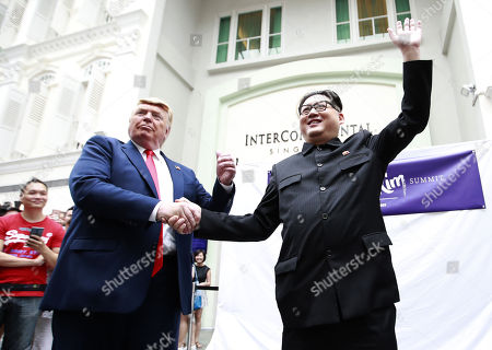 Kim Jong-un impersonator Howard X (R) and Donald Trump impersonator Dennis Alan (L) pose making a hand-shake as they make an appearance at the Bugis Junction shopping mall in Singapore, 09 June 2018. US President Donald J. Trump and North Korean leader Kim Jong-un are scheduled to meet at the Capella Hotel on Singapore's Sentosa Island for an historic summit on 12 June 2018.