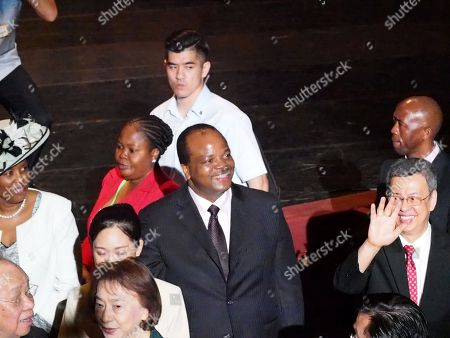Stock Image of King Mswati III (C) of Swatini, formerly known as Swaziland, accompanied by Queen LaMotsa (L) and Taiwan's Vice President Chen Chien-jen (R), waves to students while attending the graduation ceremony of his son, Prince Buhlebenkhosi from the Shih Chien University, in Taipei, Taiwan, 09 June 2018.The King also received an honorary doctorate degree from the Shih Chien Univesrity. During his speech, King Mswati III said 'The nation of eSwatini will remain friends with Taiwan for generations.' The Kingdom of eSwatini is one of the 12 countries recognizing Taiwan and is Taiwan's only African ally after Burkina Faso dropped Taipei to recognize Beijing in May. Chinese Foreign Minister Wang Yi also in May called on eSwatini to launch diplomatic ties with China before Beijing hosts a summit of African leaders in early September.