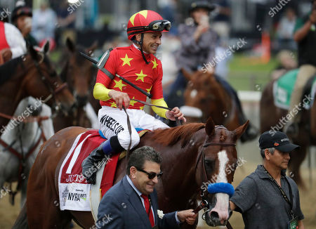 Jockey Mike Smith rides Justify to the winner's circle led by assistant trainer Jimmy Barnes, left, and Carlos Martin after winning the 150th running of the Belmont Stakes horse race and the Triple Crown, in Elmont, N.Y