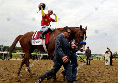 Assistant trainer Jimmy Barnes leads Justify to the winner's circle as jockey Mike Smith celebrates after winning the Triple Crown at the150th running of the Belmont Stakes horse race, in Elmont, N.Y