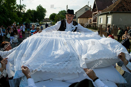 A reveller wearing a folk costume stacks the bride's bedding onto a horse cart during the 10th annual traditional peasant wedding event in Szilhalom, 125 kms northeast of Budapest, Hungary, 09 June 2018. The cultural and gastronomic folk festival runs for three days.
