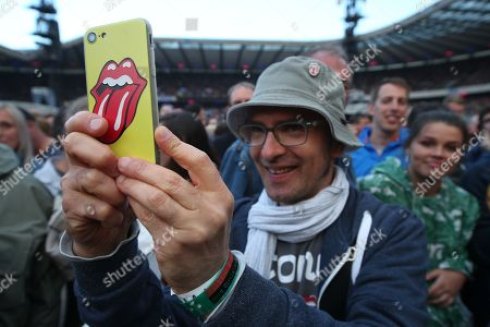 The Rolling Stones - Italian concert-goer Massimiliano Luna takes a photograph with a smartphone in Rolling Stones case