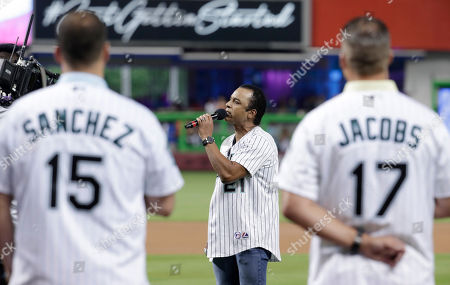 Jon Secada sings the national anthem before a baseball game between the Miami Marlins and the San Diego Padres, in Miami. Former Florida Marlins players Gaby Sanchez (15) and Mike Jacobs (17) stand on the field. The Marlins are celebrating their 25th anniversary this weekend