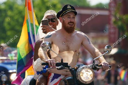 Scott Simpson, Michael Clarke. Scott Simpson, foreground, and his husband Michael Clarke ride with the Out Riders Women's Motorcycle Club, going as Prince Harry and Meghan Markle, in the Capital Pride Parade in Washington, . The yearly event is hosted by and in support of the the LGBTQ+ community and moves through the Dupont and Logan Circle neighborhoods of Washington