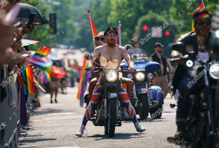 Scott Simpson, Michael Clarke. Scott Simpson and his husband, Michael Clarke, ride with the Out Riders Women's Motorcycle Club, as Prince Harry and Meghan Markle in the Capital Pride Parade in Washington, . The yearly event is hosted by and in support of the LGBTQ+ community and moves through the Dupont Circle and Logan Circle neighborhoods of Washington