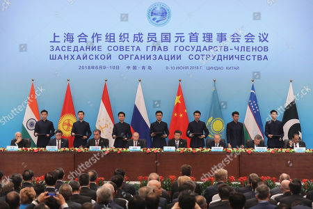 (L-R) Indian Prime Minister Narendra Modi, Kyrgyzstan's President Sooronbay Jeenbekov, Tajikistan's President Emomalii Rahmon, Russian President Vladimir Putin, Chinese President Xi Jinping, Kazakhstan's President Nursultan Nazarbayev, Uzbekistan's President Shavkat Mirziyoyev and Pakistan's President Mamnoon Hussain, sign during the signing ceremony ahead a joint press conference of the Heads of SCO Member States during the 18th Shanghai Cooperation Organization (SCO) Summit in Qingdao city, Shandong province, China, 10 June 2018. The 18th Shanghai Cooperation Organization Summit is held in Qingdao from 09 to 10 June 2018.