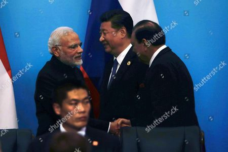 """Indian Prime Minister Narendra Modi, left, shakes hands with Pakistan President Mamnoon Hussain, right, next to Chinese President Xi Jinping, center, after a joint press conference for the Shanghai Cooperation Organization (SCO) Summit in Qingdao in eastern China's Shandong Province, . Xi extolled free trade and criticized """"selfish, short-sighted"""" policies during the closely orchestrated gathering, standing in stark contrast with the G-7 summit that ended in disarray over trade tensions"""