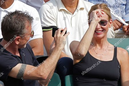 British actor and director Tim Roth takes a picture of his wife Nikki Butler when watching the men's final match of the French Open tennis tournament at the Roland Garros stadium in Paris, France