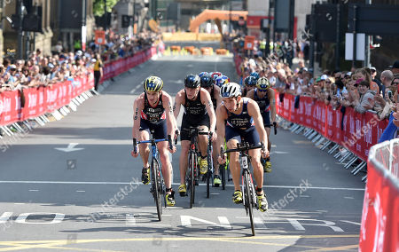 The Peloton races through the streets of Leeds with  Jonathan Brownlee GBR inside left and  Pierre Le Corre FRA leading him out