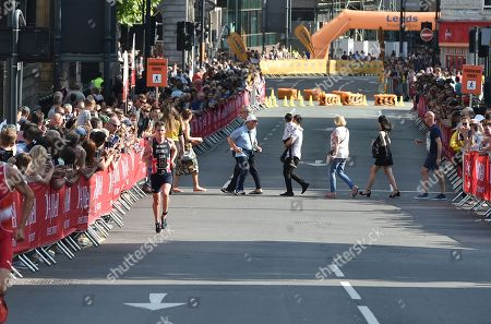 Jonathan Brownlee GBR brings up the rear of the race before dropping out through illness