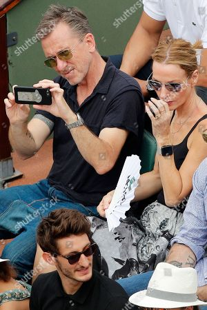 British actor Tim Roth and his wife Nikki Butler watch the men's final match of the French Open tennis tournament at the Roland Garros stadium, in Paris. Below is French actor Pierre Niney