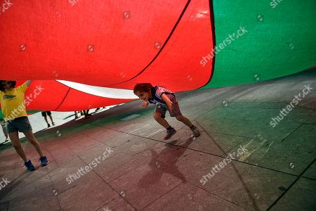 92d2bbc931 A boy runs under a giant Basque flag or   Ikurrina