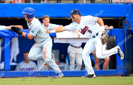 Auburn infielder Brendan Venter, right, tags out Florida infielder Deacon Liput, left, on the third base line during the eighth inning of an NCAA Super Regional college baseball game, in Gainesville, Fla