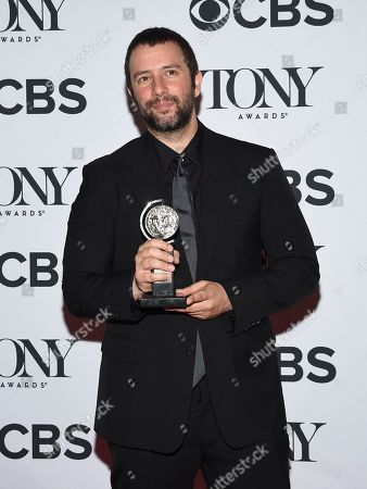 """Itamar Moses poses in the press room with the award for book of a musical for """"The Band's Visit"""" at the 72nd annual Tony Awards at Radio City Music Hall, in New York"""