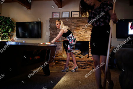 """Prostitutes Destini Starr, right, and Paris Envy play pool while waiting for customers at the Love Ranch brothel in Crystal, Nev. A coalition of religious groups and anti-sex trafficking activists have launched referendums to ban brothels in two of Nevada's seven counties where they legally operate. Legal pimp Dennis Hof, who has half a dozen brothels operating in the two counties and starred in the HBO adult reality series """"Cathouse,"""" is challenging incumbent Assembly member James Oscarson of Pahrump in a Republican primary Tuesday, June 12"""