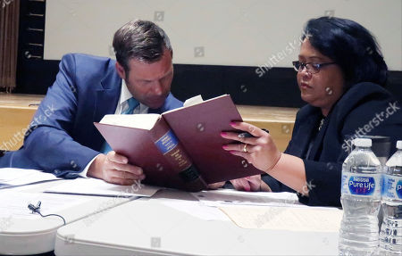 Kansas Secretary of State Kris Kobach, left, confers with Deputy Attorney General Athena Andaya, right, over state election laws during a meeting of the State Objections Board, in Topeka, Kan. The board has decided to list two candidates with the same first and last names in a Republican congressional primary as Rep. Ron Estes and Ron M. Estes