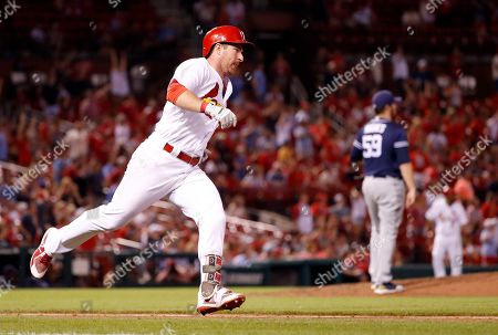 St. Louis Cardinals' Jedd Gyorko, left, rounds the bases after hitting a solo home run off San Diego Padres relief pitcher Phil Hughes during the eighth inning of a baseball game, in St. Louis