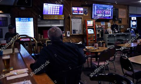 John Miller, of Manchester, N.H., a former U.S. Army sergeant who served as a forward radio relay operator in Vietnam, watches as President Donald Trump shakes hands with North Korean leader Kim Jong Un, while having a beer at the American Legion Post #2 in Manchester on
