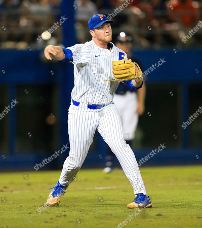 Florida pitcher Michael Byrne throws to first for an out after fielding a ground ball during an NCAA Super Regional college baseball game against Auburn, in Gainesville, Fla