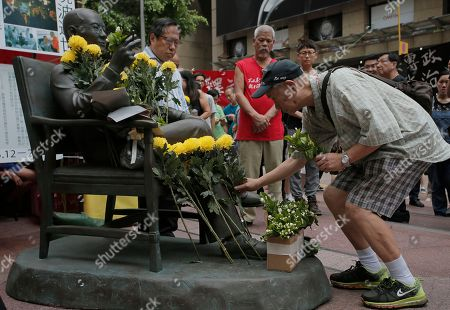 A man places flowers on a statue of the late Chinese Nobel Peace laureate Liu Xiaobo during an unveiling ceremony in Hong Kong, . Activists urged the Chinese government to release iu Xiaobo's detained wife Liu Xia