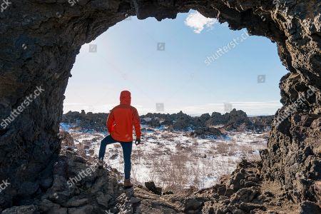 MODEL RELEASED Man in a rock arch, volcanic landscape, Krafla volcanic area, Dimmuborgir National Park, Myvatn, Iceland