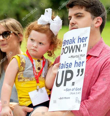 Chase Crawford, a Southern Baptist Convention messenger from Arkansas, and his 2-year-old daughter Chloe Jean Crawford listen to speakers during a rally protesting the Southern Baptist Convention's treatment of women on outside the convention's annual meeting at the Kay Bailey Hutchison Convention Center in Dallas
