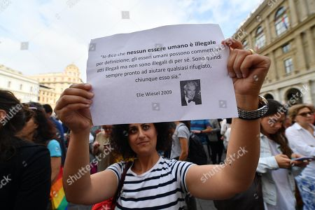 A demostrator holds a banner citing Romanian-born American Jewish writer, professor, political activist, Nobel Laureate and Holocaust survivor Elie Wiesel during the demonstration 'Apriamo i porti. Garantiamo il soccorso in mare' (Let the harbors open. We guarantee rescue at sea) against the migration policy of the new government, in Genoa, Italy, 12 June 2018.