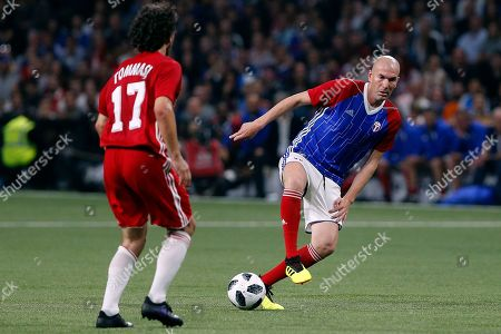 Former Real Madrid head coach Zinedine Zidane, right, challenges for the ball with Damiano Tommasi of Italy during a charity soccer match between members of the 1998 World Cup winning French team and a team of international veteran players who were also involved in the same tournament, at the U Arena in Nanterre, north of Paris, France