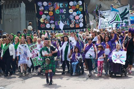 Stock Image of Piper Louise Marshall leads PROCESSIONS in Edinburgh  with marchers donning the colours of the suffragette movement - green, white and violet finishing at Holyrood, Holyrood, Edinburgh, Scotland.