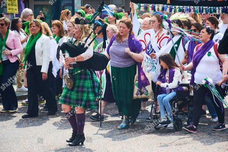 Piper Louise Marshall leads PROCESSIONS in Edinburgh  with marchers donning the colours of the suffragette movement - green, white and violet finishing at Holyrood, Holyrood, Edinburgh, Scotland.