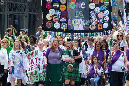 Stock Picture of Piper Louise Marshall leads PROCESSIONS in Edinburgh  with marchers donning the colours of the suffragette movement - green, white and violet finishing at Holyrood, Holyrood, Edinburgh, Scotland.