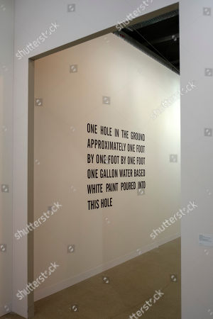 """The artwork """"One Hole In The Ground Approximately One Foot By One Foot By One Foot One Gallon Water Based White Paint Poured Into This Hole"""" (1968) by American artist Lawrence Weiner is on display at the international art show Art Basel, in Basel, Switzerland, 13 June 2018."""