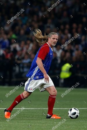 France's Emmanuel Petit runs with the ball during a charity soccer match between members of the 1998 World Cup winning French team and a team of international veteran players who were also involved in the same tournament, at the U Arena in Nanterre, north of Paris, France