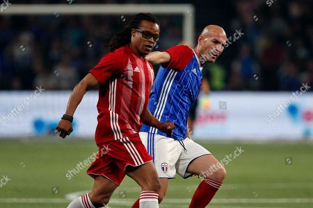 Stock Photo of Former Real Madrid head coach Zinedine Zidane, right, challenges for the ball with Edgar Davids of Netherland during a charity soccer match between members of the 1998 World Cup winning French team and a team of international veteran players who were also involved in the same tournament, at the U Arena in Nanterre, north of Paris, France
