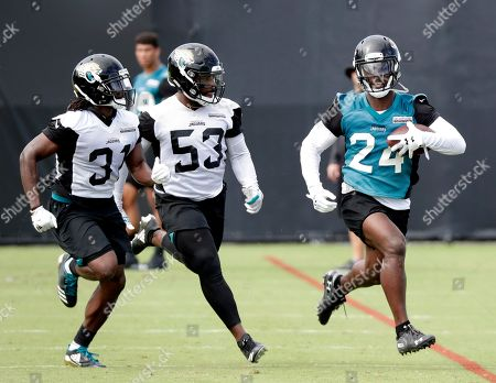 Jacksonville Jaguars running back T.J. Yeldon (24) runs past cornerback Jalen Myrick (31) and linebacker Blair Brown (53) after a reception during an NFL football practice, in Jacksonville, Fla