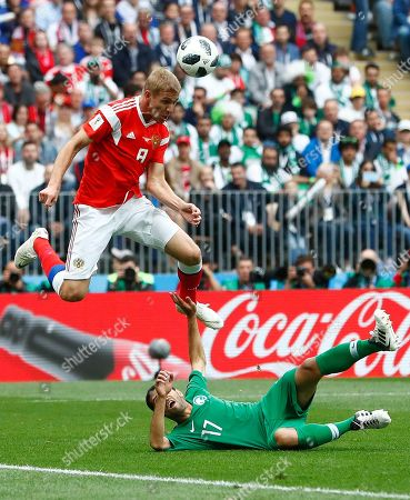 Russia's Yuri Gazinsky heads the ball to score the opening goal during the group A match between Russia and Saudi Arabia which opens the 2018 soccer World Cup at the Luzhniki stadium in Moscow, Russia
