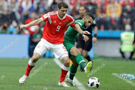 Russia's Alan Dzagoev, left, and Saudi Arabia's Mohammed Alburayk challenge for the ball during the group A match between Russia and Saudi Arabia which opens the 2018 soccer World Cup at the Luzhniki stadium in Moscow, Russia