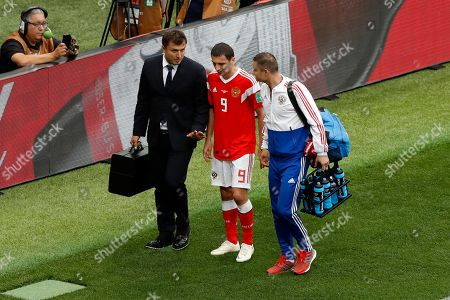 Russia's Alan Dzagoev, center, leaves the pitch after his injury during the group A match between Russia and Saudi Arabia which opens the 2018 soccer World Cup at the Luzhniki stadium in Moscow, Russia