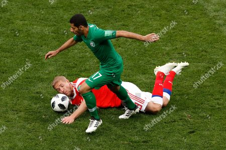 Taiseer Aljassam, Yuri Gazinsky. Saudi Arabia's Taiseer Aljassam, foreground, keeps the ball as Russia's Yuri Gazinsky falls down during the group A match between Russia and Saudi Arabia which opens the 2018 soccer World Cup at the Luzhniki stadium in Moscow, Russia