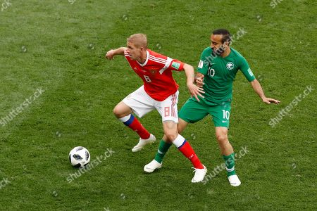 Yuri Gazinsky, Mohammed Alsahlawi. Russia's Yuri Gazinsky, left, controls the ball as Saudi Arabia's Mohammed Alsahlawi tries to stop him during the group A match between Russia and Saudi Arabia which opens the 2018 soccer World Cup at the Luzhniki stadium in Moscow, Russia