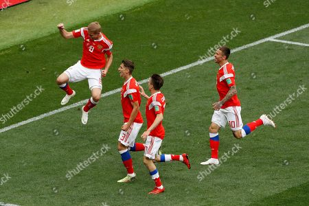 Russia's Yuri Gazinsky, left, celebrates with his teammates after scoring the opening goal of his team during the group A match between Russia and Saudi Arabia which opens the 2018 soccer World Cup at the Luzhniki stadium in Moscow, Russia