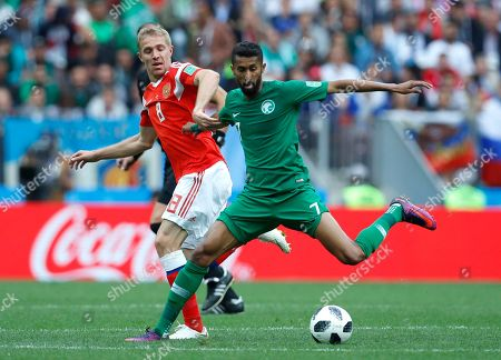 Russia's Yuri Gazinsky, left, challenges for the ball with Saudi Arabia's Salman Alfaraj during the group A match between Russia and Saudi Arabia which opens the 2018 soccer World Cup at the Luzhniki stadium in Moscow, Russia