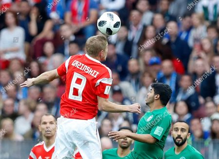 Russia's Yuri Gazinsky, left, jumps for the ball with Saudi Arabia's Yahia Alshehri during the group A match between Russia and Saudi Arabia which opens the 2018 soccer World Cup at the Luzhniki stadium in Moscow, Russia