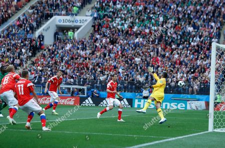 Russia's Yuri Gazinsky, left, scores the opening goal of his team as Saudi Arabia goalkeeper Abdullah Almuaiouf tries to stop the ball during the group A match between Russia and Saudi Arabia which opens the 2018 soccer World Cup at the Luzhniki stadium in Moscow, Russia