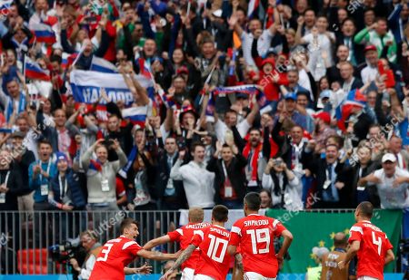 Russia's Yuri Gazinsky celebrates with teammates after scoring his side's opening goal during the group A match between Russia and Saudi Arabia which opens the 2018 soccer World Cup at the Luzhniki stadium in Moscow, Russia
