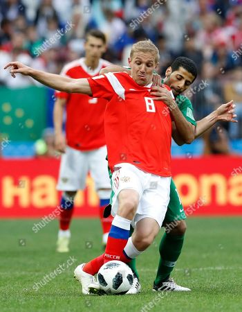 Russia's Yuri Gazinsky, front defends the ball from Saudi Arabia's Taiseer Aljassam during the group A match between Russia and Saudi Arabia which opens the 2018 soccer World Cup at the Luzhniki stadium in Moscow, Russia