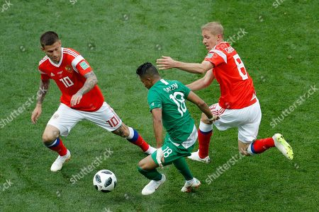 Saudi Arabia's Salem Aldawsari, center, is challenged for the ball by Russia's Fyodor Smolov, left, and Yuri Gazinsky during the 2018 soccer World Cup opening match at the Luzhniki stadium in Moscow, Russia