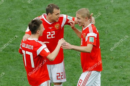 Russia's Alexander Golovin, left, is greeted by teammates Yuri Gazinsky, right, and Artyom Dzyubathe after scoring his side fifth goal agains Saudi Arabia during their group A match which opened the 2018 soccer World Cup at the Luzhniki stadium in Moscow, Russia