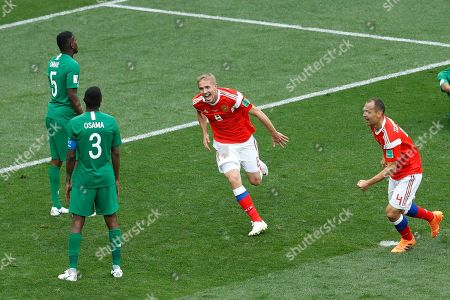 Russia's Yuri Gazinsky celebrates scoring his side's first goal against Saudi Arabia during the group A match that opened the 2018 soccer World Cup at the Luzhniki stadium in Moscow, Russia